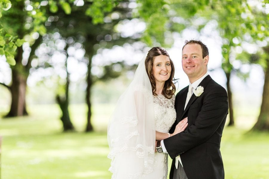 bride and groom in garden at a llansantffraed court wedding on a sunny day