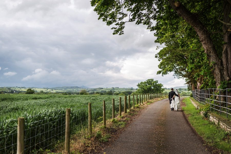 bride and groom walking down the drive at llansantffraed court wedding with green field and hills in background