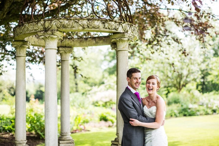 bride and groom on summers day hugging and laughing by a folly at miskin manor