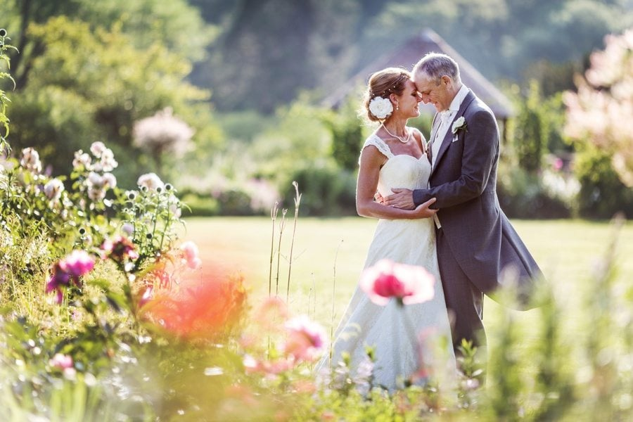 bride and groom kissing behind flower bed at a wedding in miskin manor, south wales