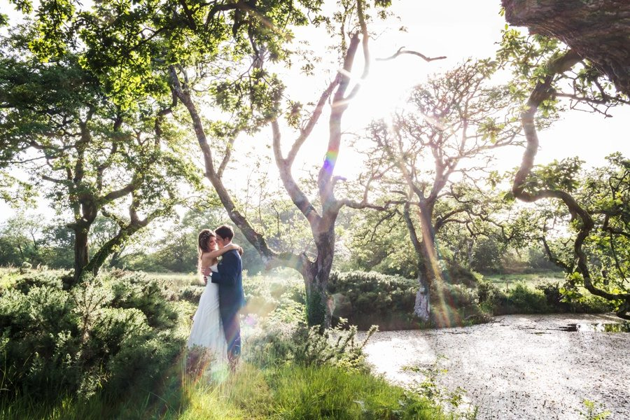 bride and groom standing in filed at oldwalls wedding in strong sunlight