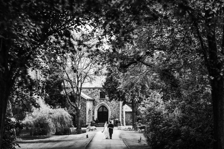 bride and groom walking down the drive ay pencoed house near cardiff, south wales