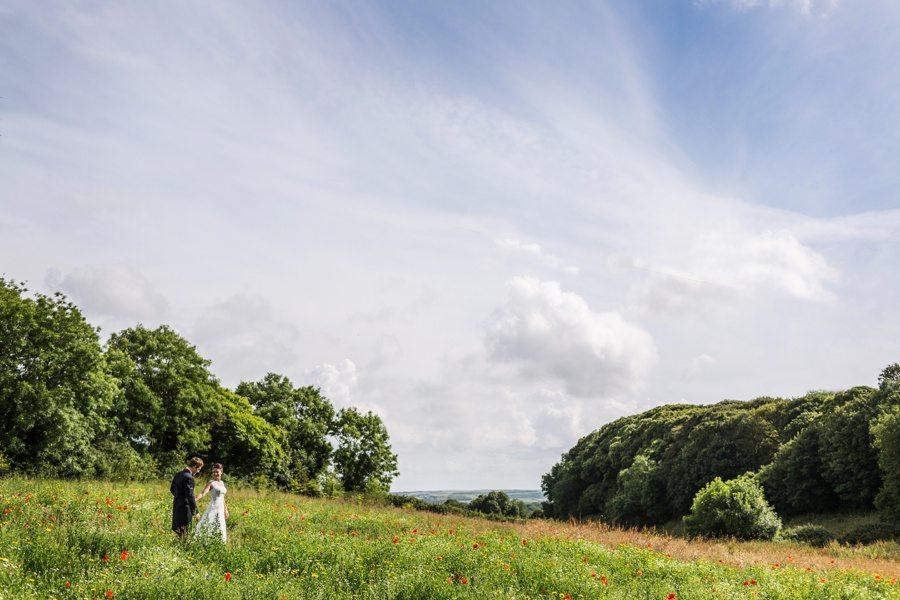 bride and groom walking in flower field at ash barton manor, devon