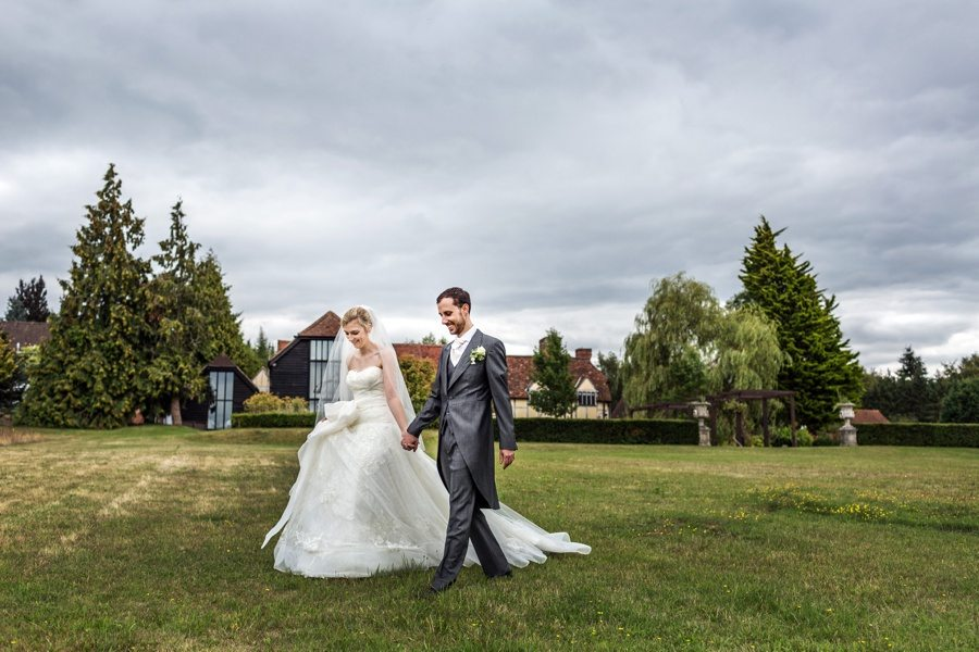 Bride and groom walking across the lawn at Cain Manor, Hampshire