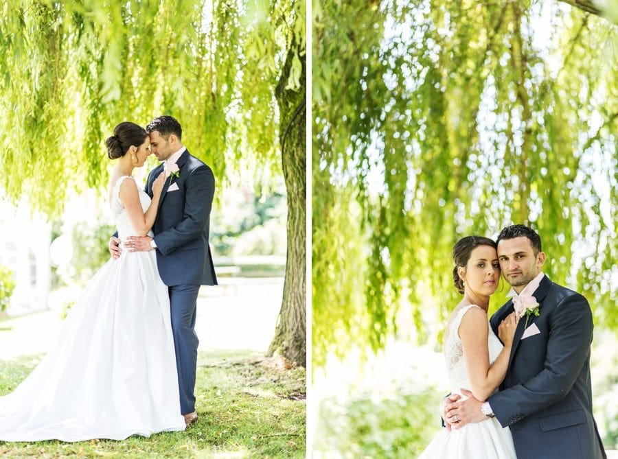 wedding couple standing under sunlight weepoing willow at the stonemill restaurant in monmouthshire