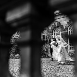 groom helps bride with her dress at a margam orangery wedding