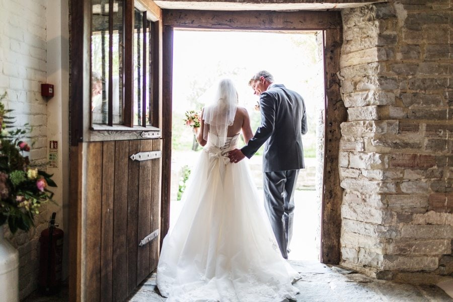 bride and groom leaving through sunlit door at a almonry barn wedding