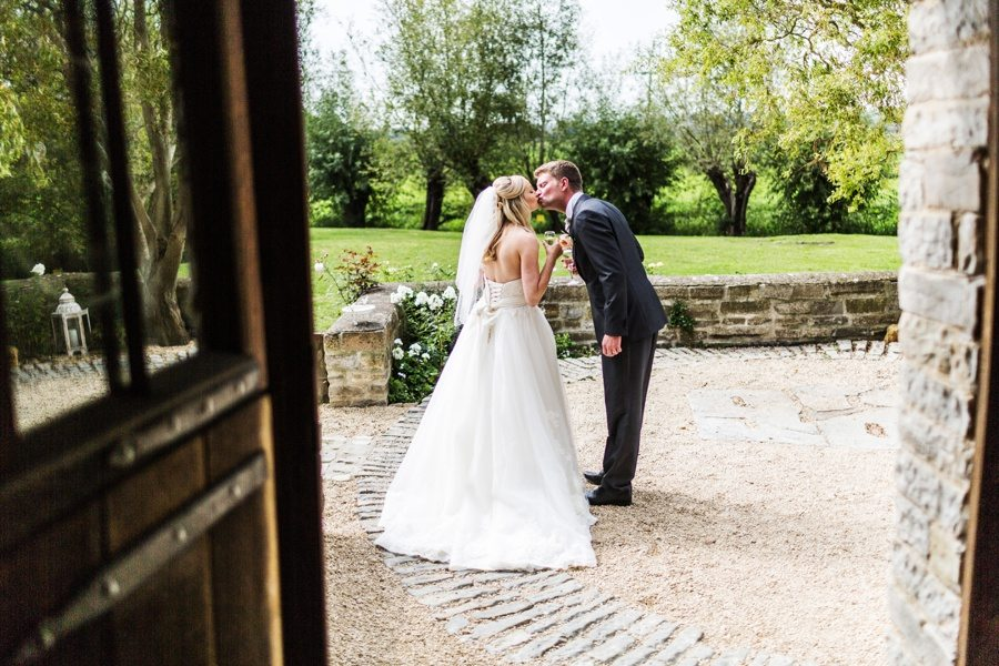 bride and groom kissing photographed through a door at a almonry barn wedding