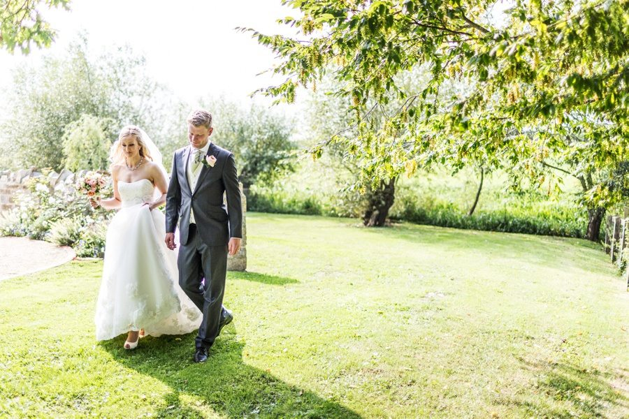bride and groom walking in gardens at almonry barn wedding