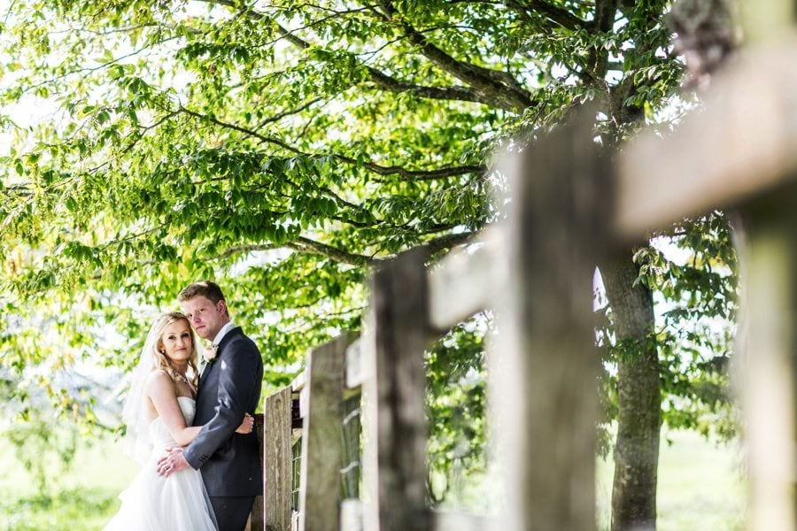 bride and groom under tree at aalmonry barn wedding