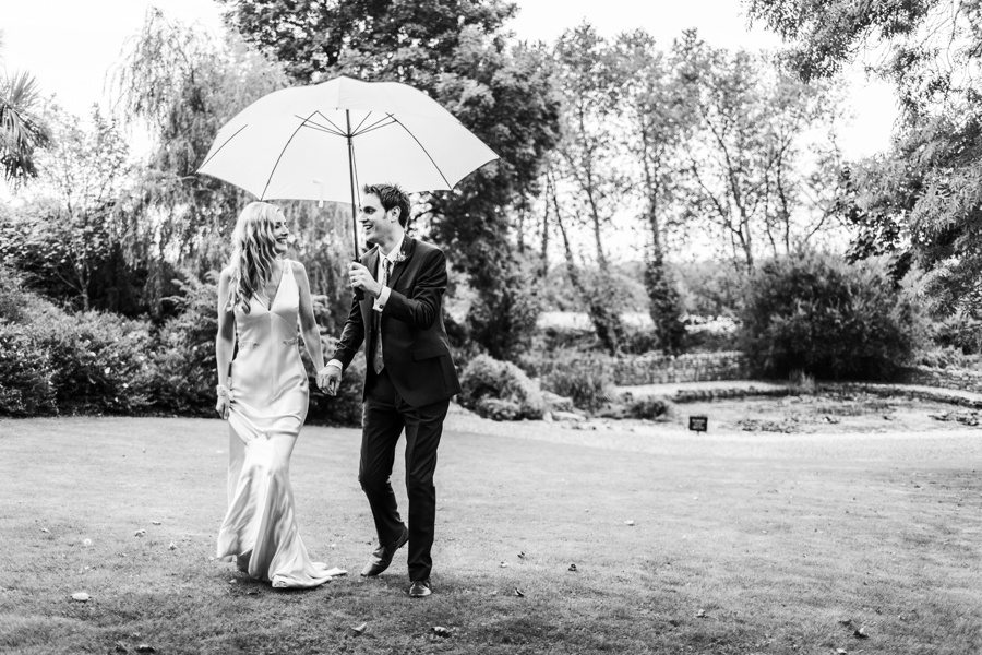 groom holding white umbrella at a king arthur hotel wedding