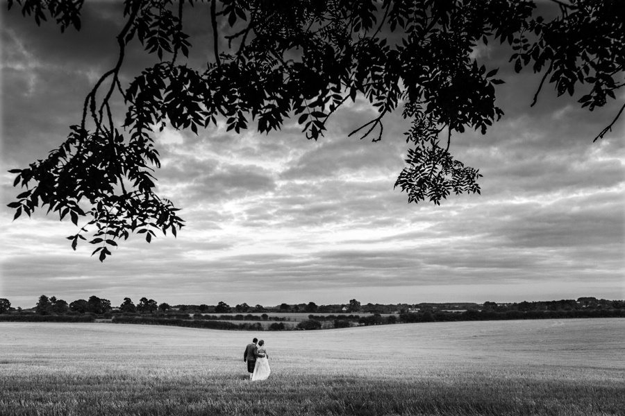 Bride and groom in field at sunrise cripps Barn Wedding