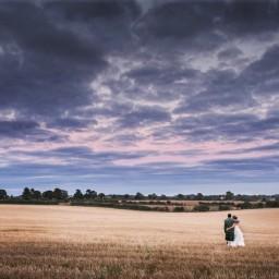 Bride and groom in field at sunrise cripps Barn Wedding