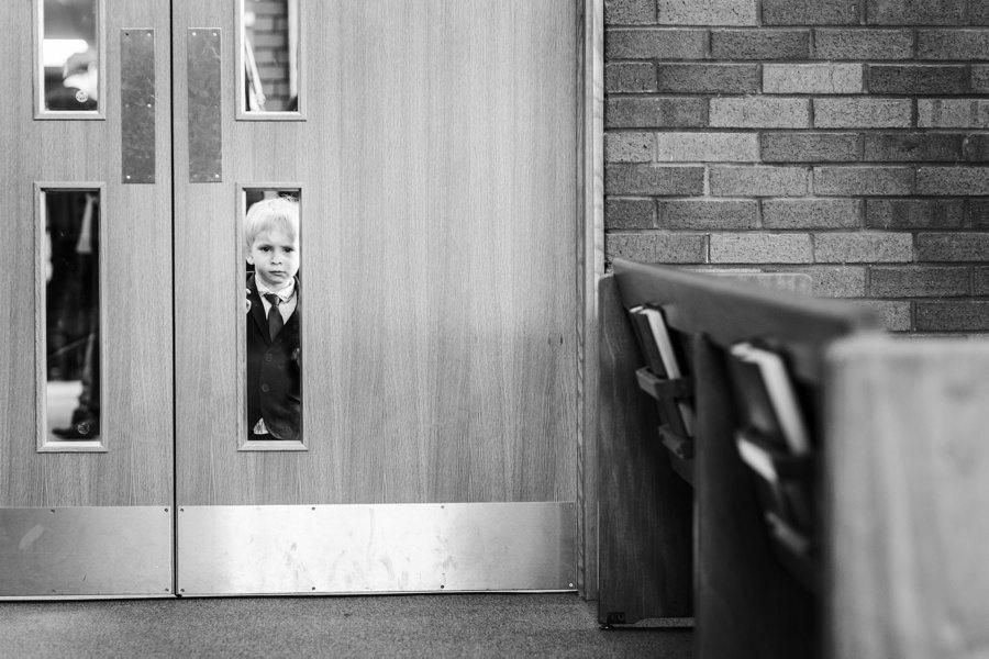 boy looking through glass door at wedding