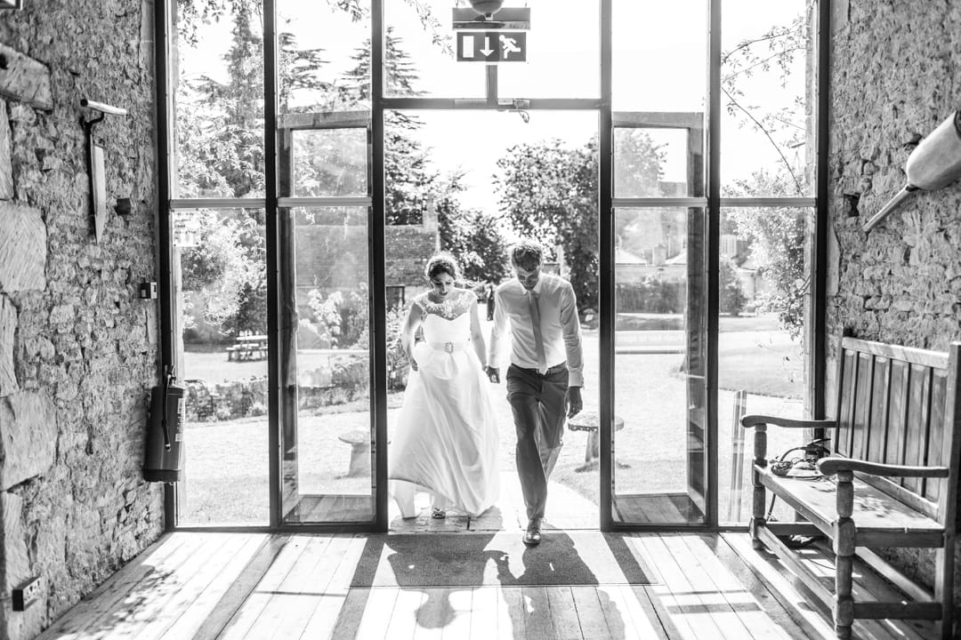 bride and groom entering great tythe barn for wedding reception