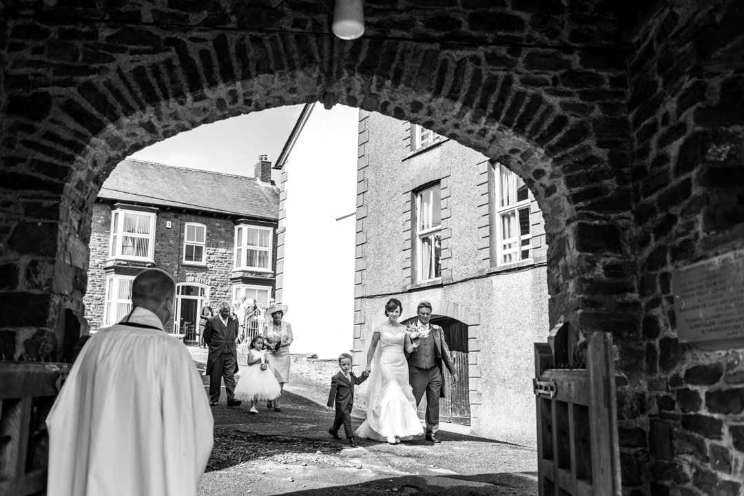Bride arriving at Groom waiting at alter of Groom laughing at Llandysul Parish Church Wedding