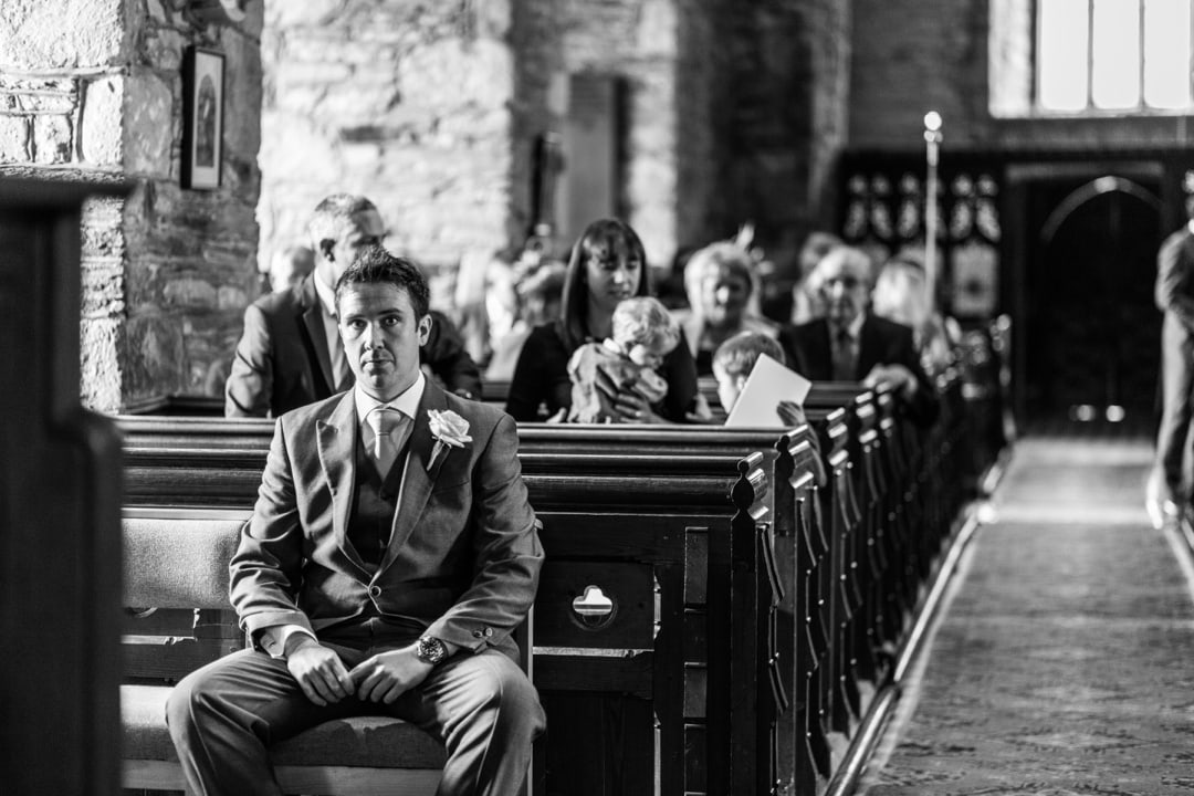 Groom waiting at alter of Groom laughing at Llandysul Parish Church Wedding