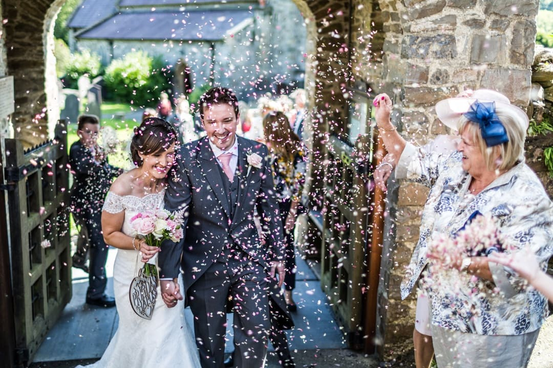 Bride and groom with confetti at Pembrokshire Church