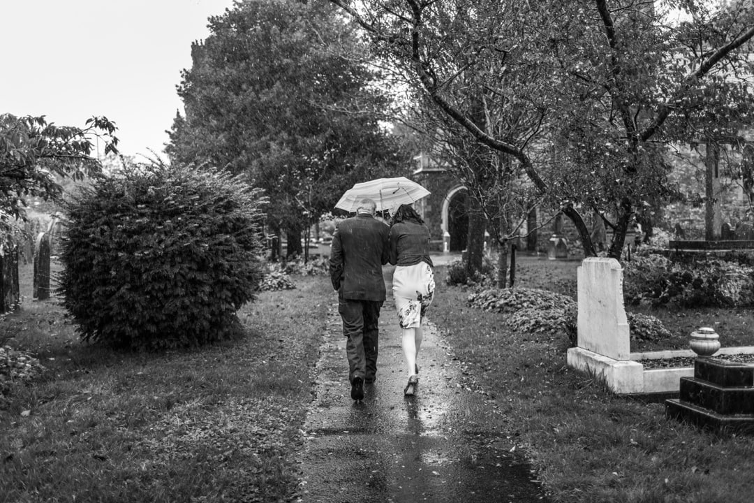 couple walkin rain at St Isaans Church in Llanishen, Cardiff
