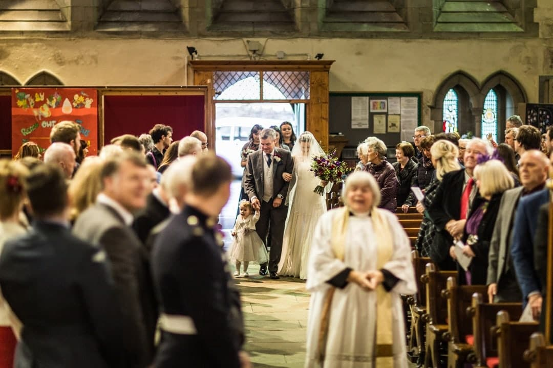 bride walks down church aisle with father