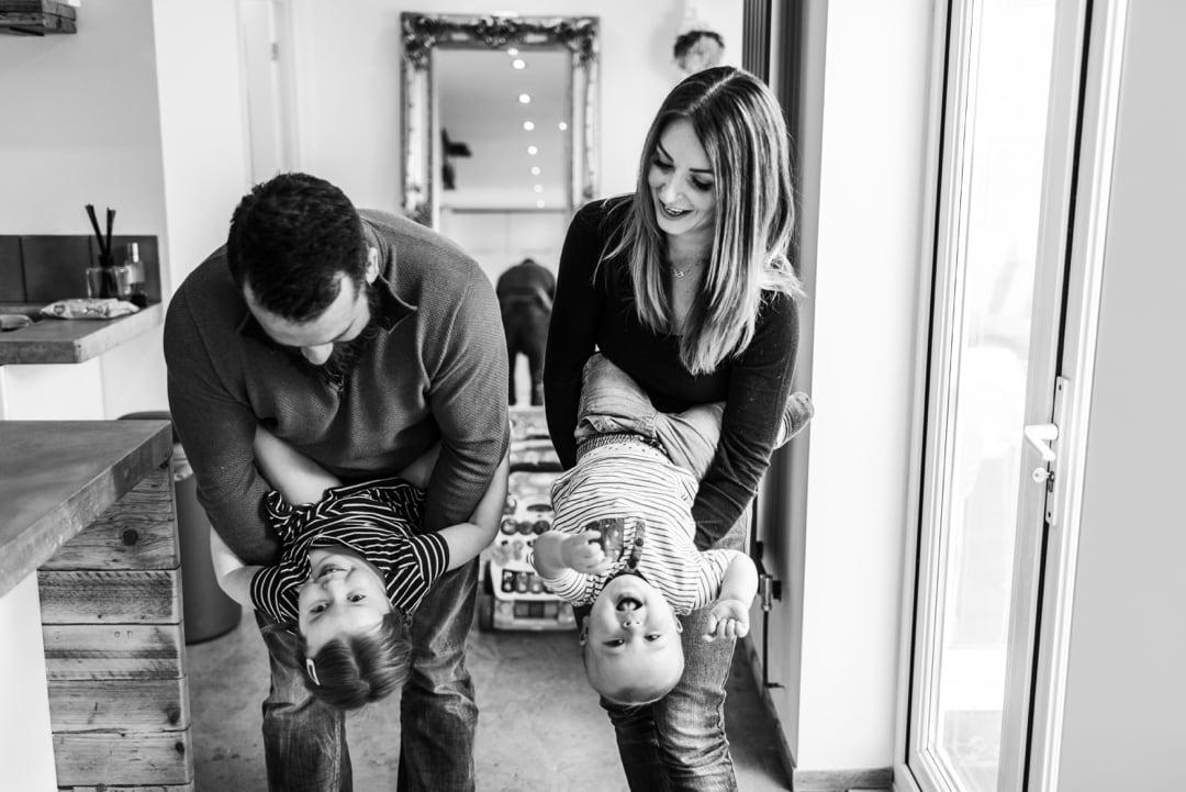 parent sholding children upside down