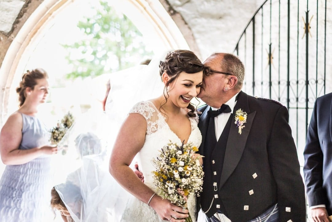 father kisses bride at church for wedding