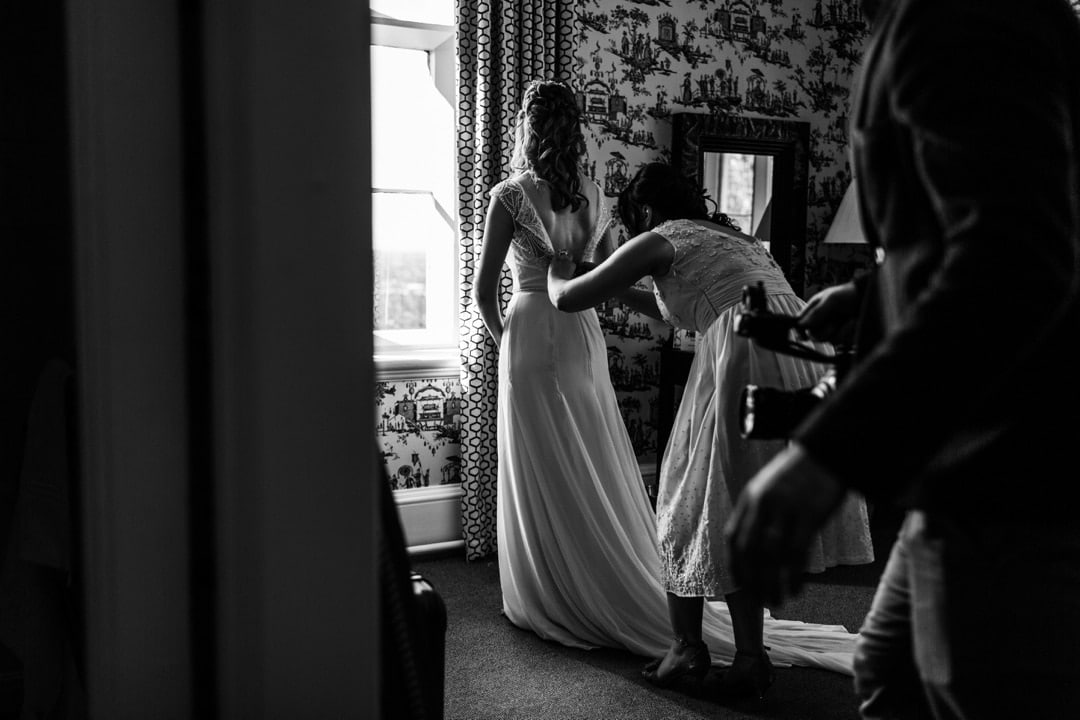 bride having dress laced up