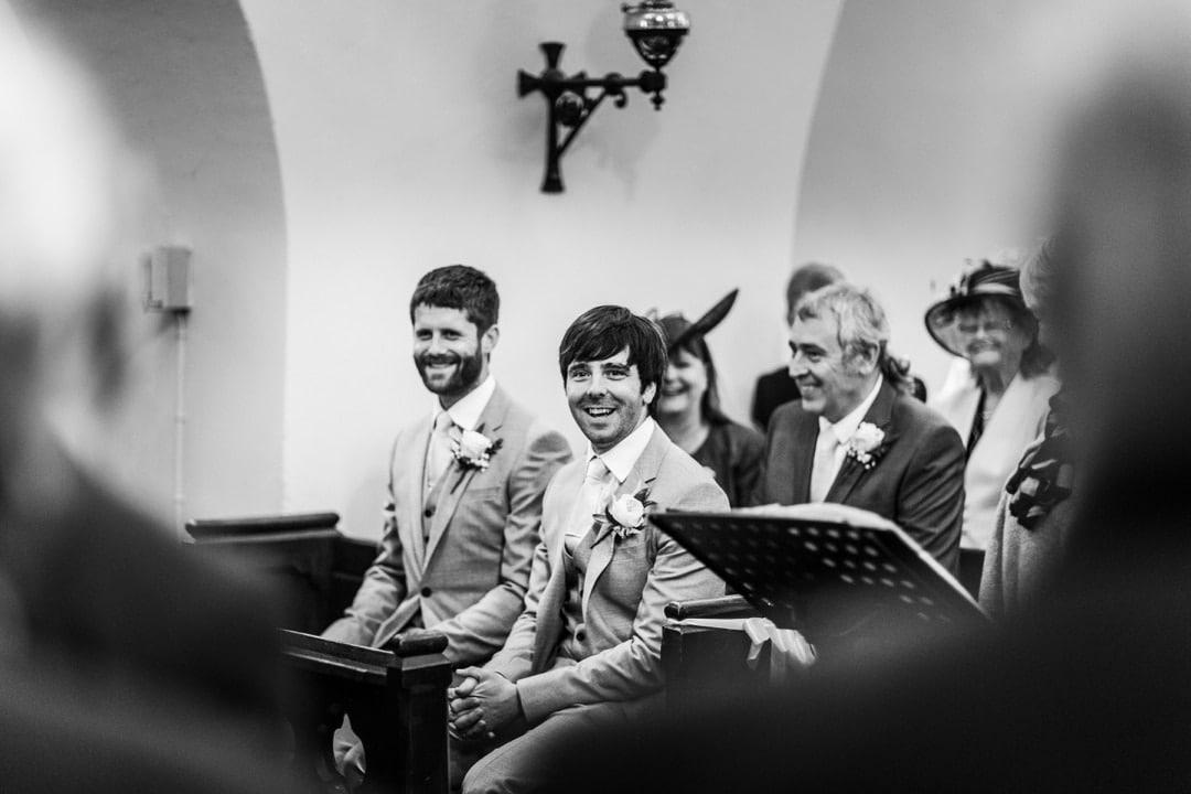 groom waits in church pew