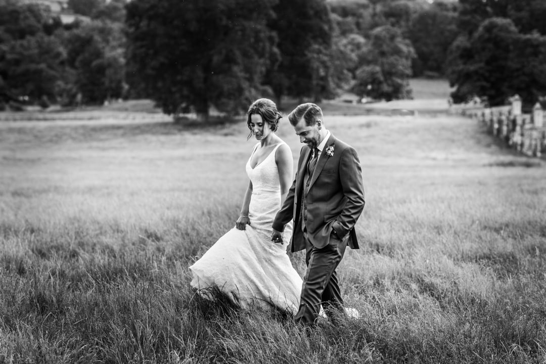 bride and groom walking in field at Glanusk Estate wedding