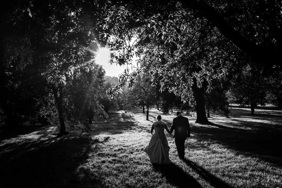 bride and groom on their wedding day walking in the evening sun at the Royal Welsh College of Music and Drama