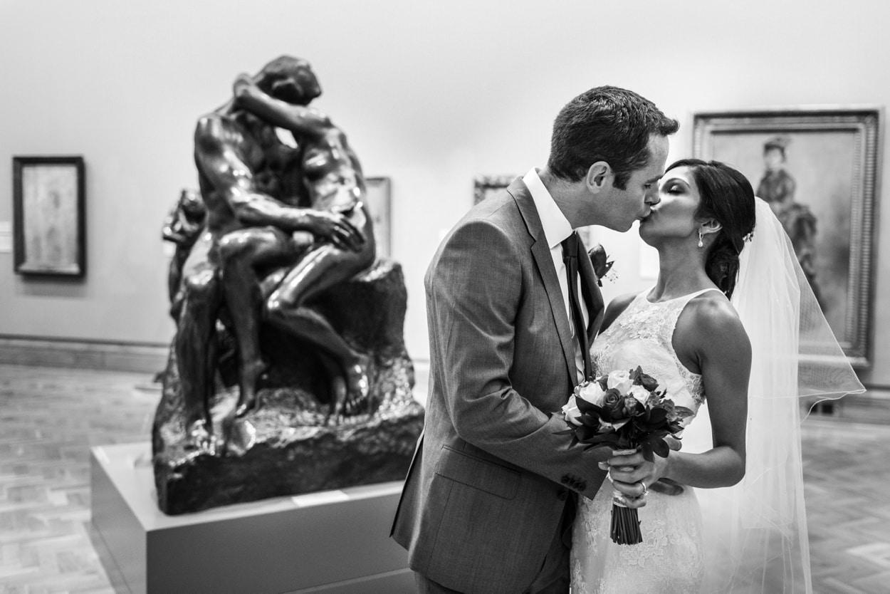 wedding day kiss next to Rodin's The Kiss