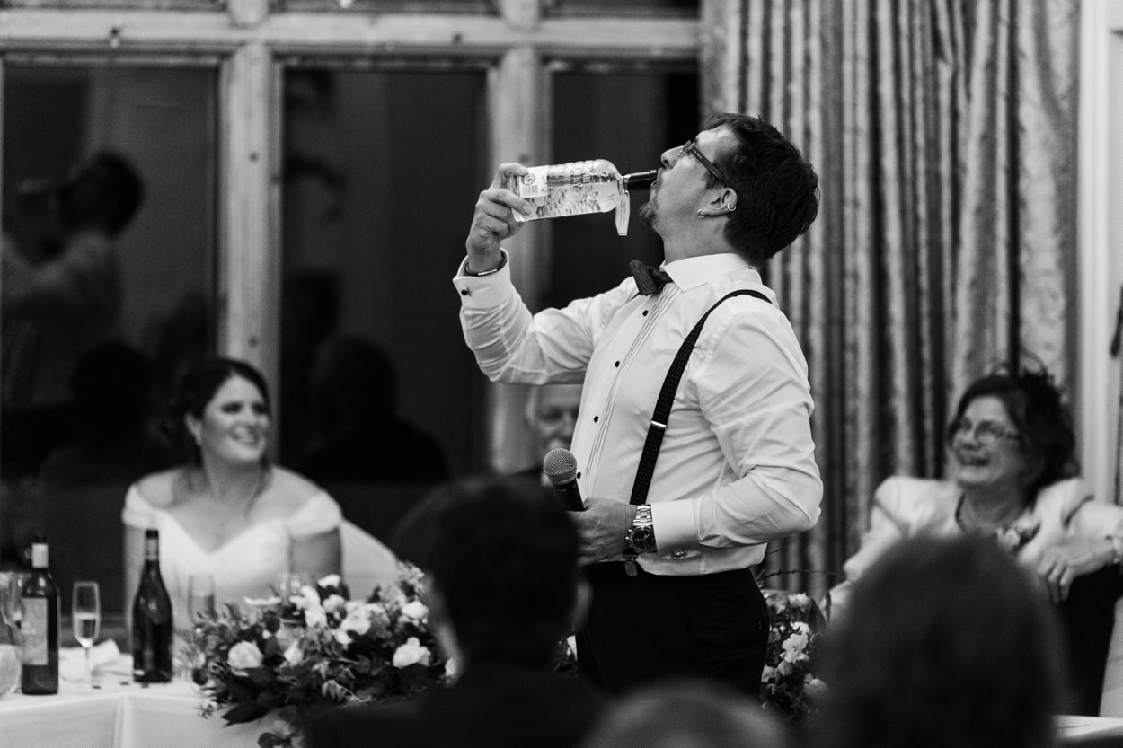 Best man drinks from bottle at Caer Llan in Monmoutshire