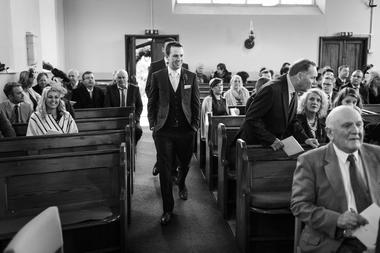 Groom walking down church aisle in West Wales