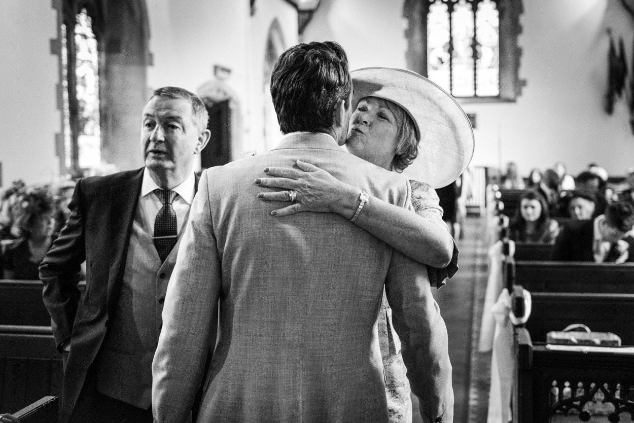 Grooms mum kissing groom