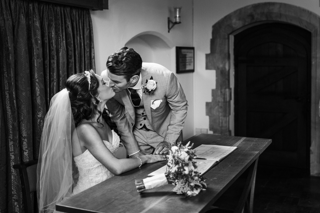 Bride and groom signing register at wedding at Christ Church in Radyr