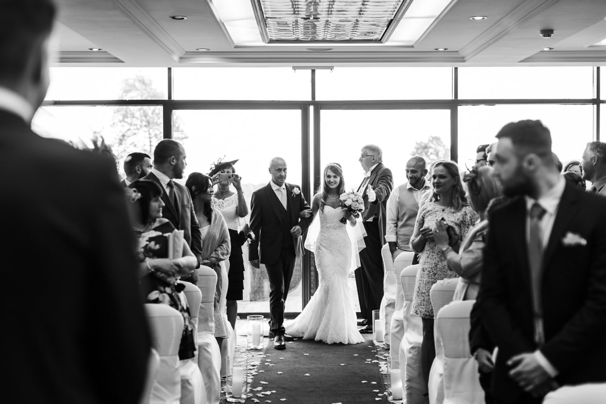 Bride and father walks in asile at The Lodge, Celtic Manor