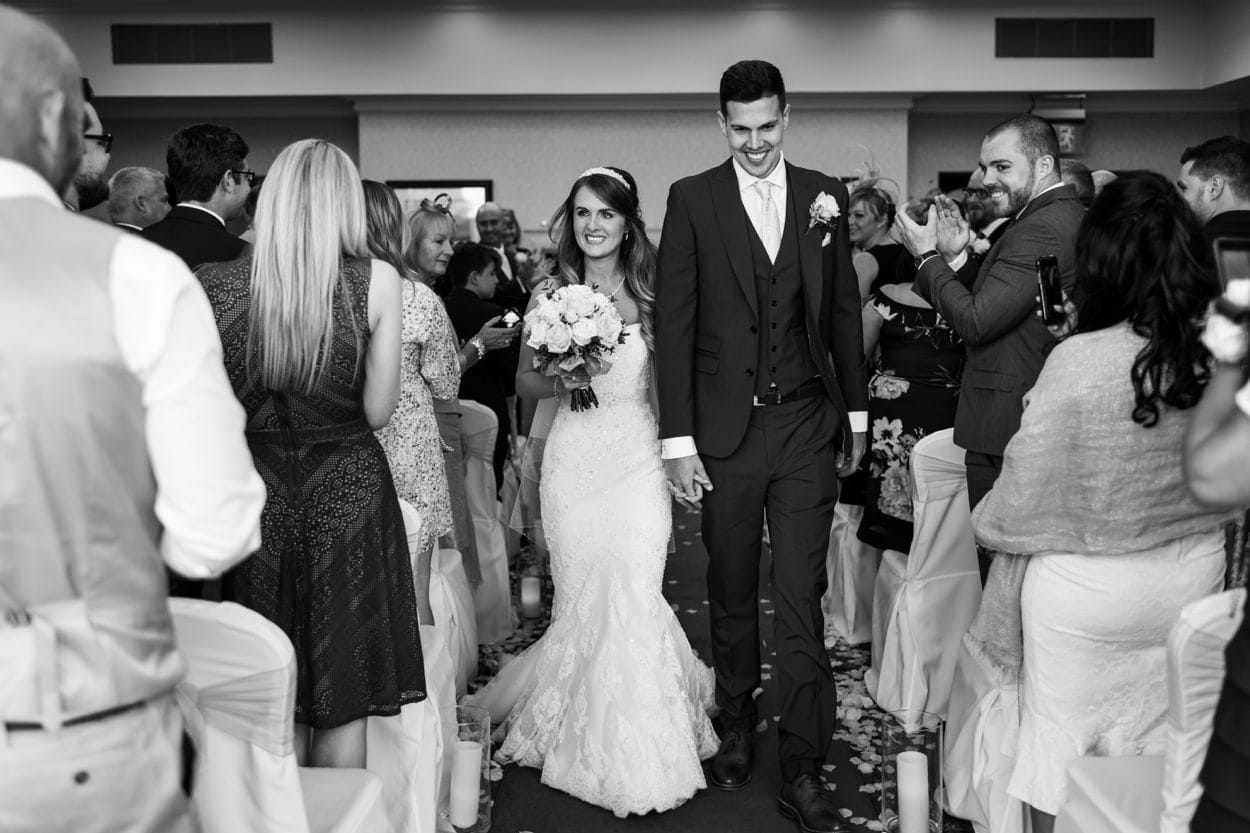 Bride and groom walk in aisle at The Lodge, Celtic Manor