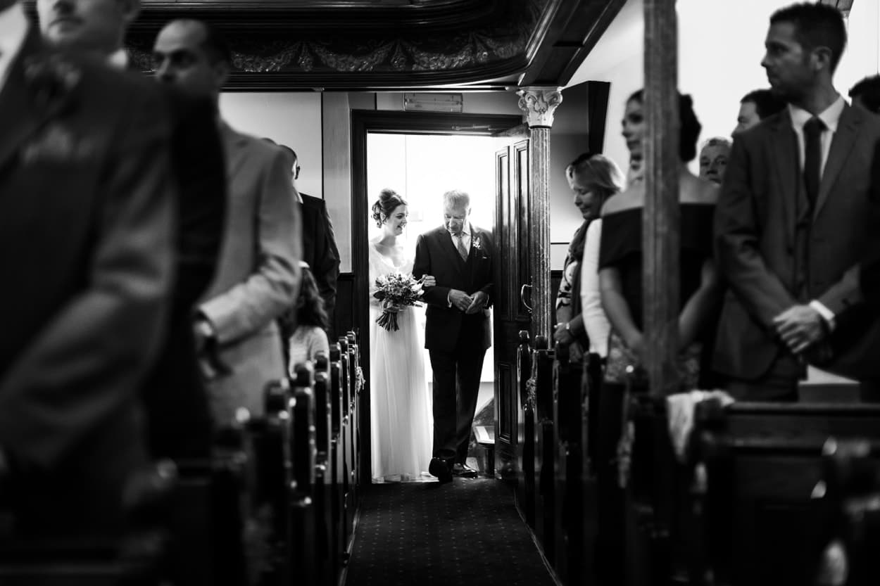 bride walks down aisle with father at Capel Newydd, Carmarthenshire