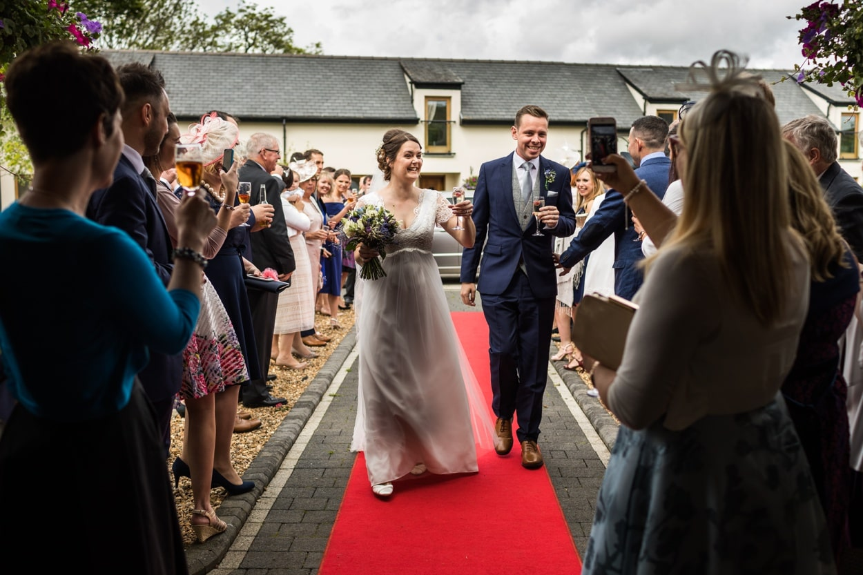 Bride and groom walk down red carpet at Oldwalls