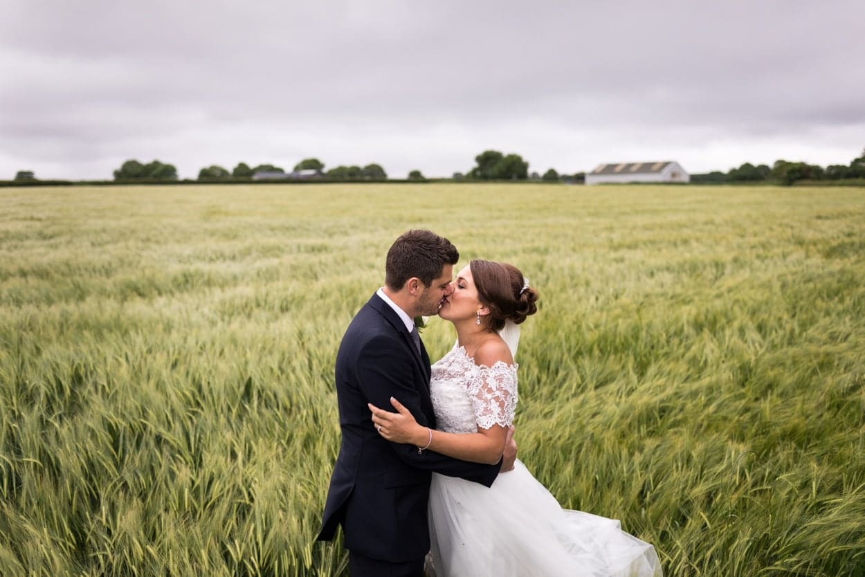 Bride and groom in field near Woodhouse Barn