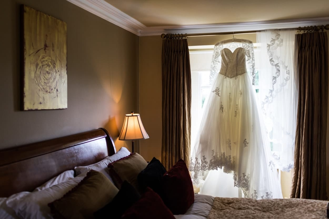 Wedding dress hanging in window at Peterstone Court in Brecon, South Wales