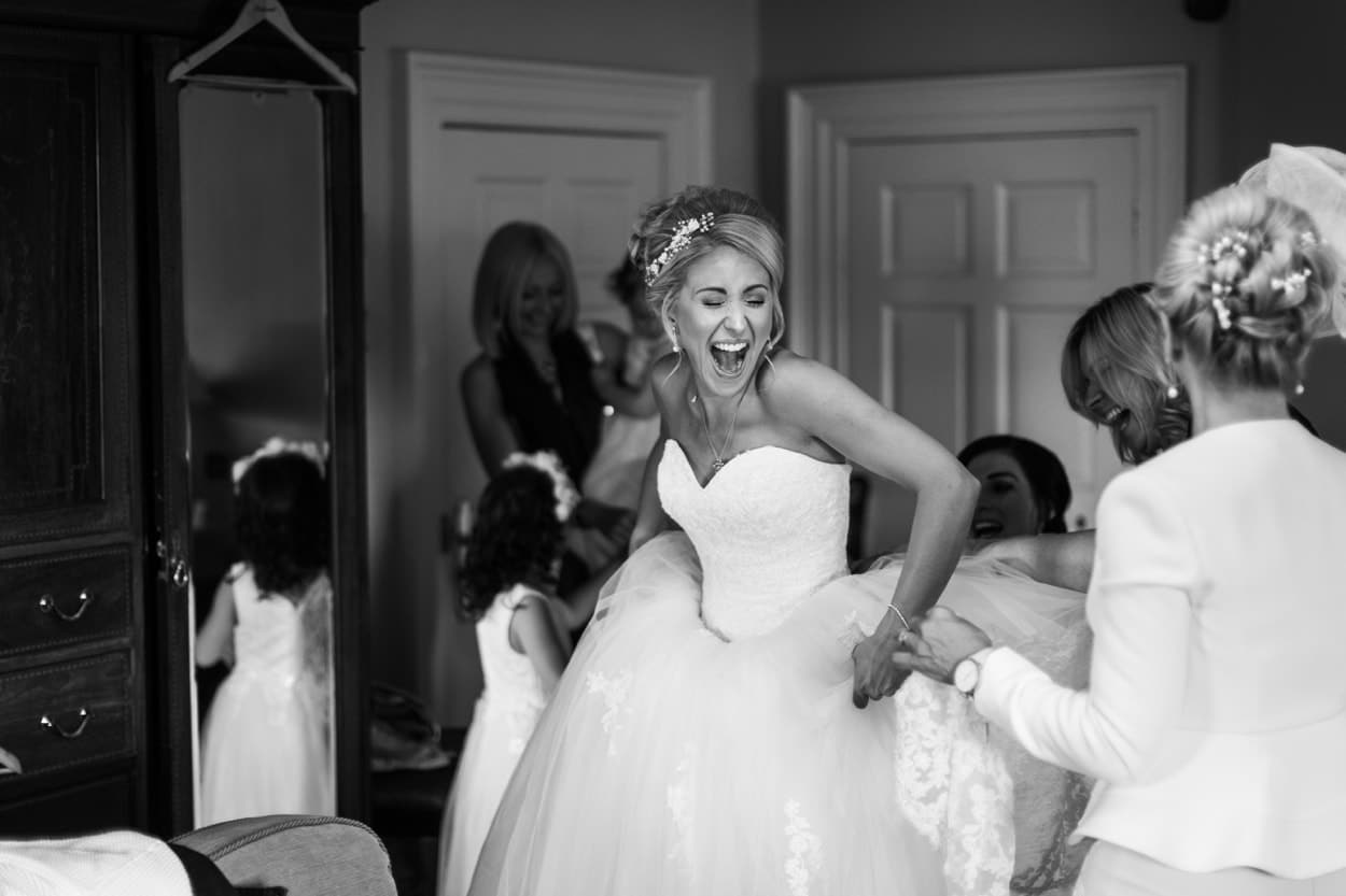 Bride puts on dress