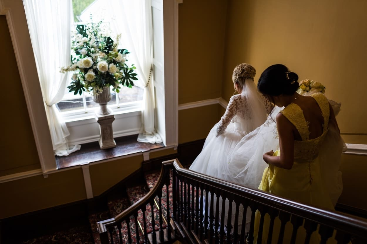 Bride descends stairs at Peterstone Court
