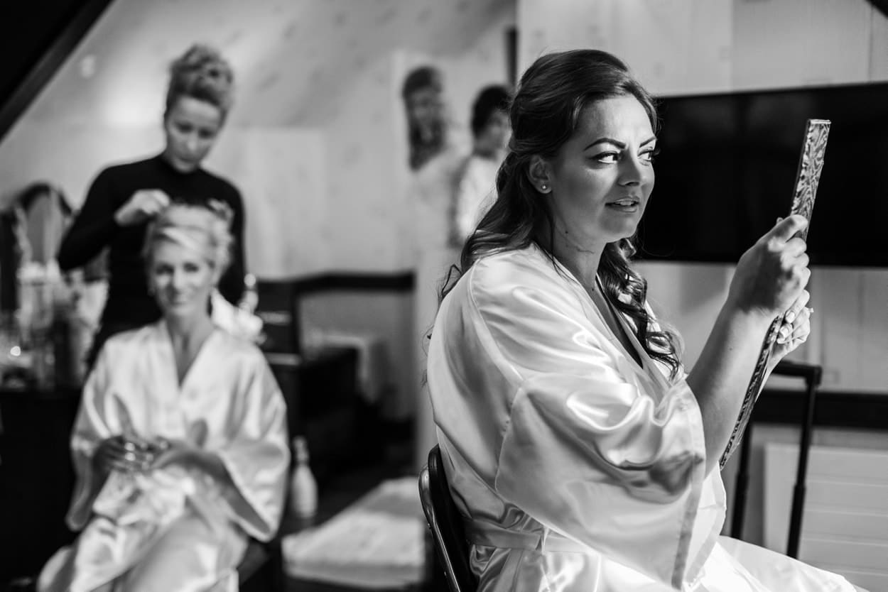 Bridesmaid inspecting hair during preparations for a Wedding at St Donats Castle