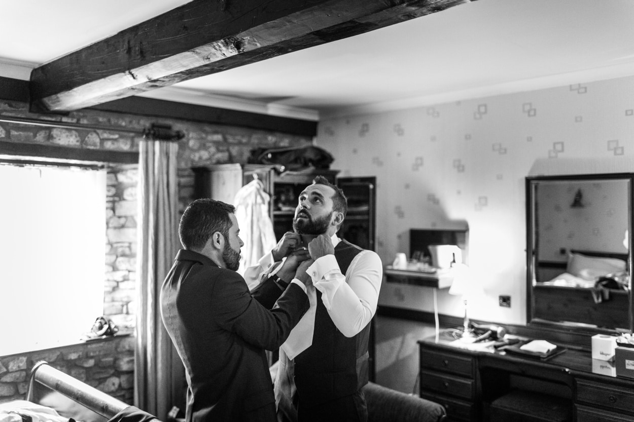 Groom having tie fitted for a Wedding at St Donats Castle