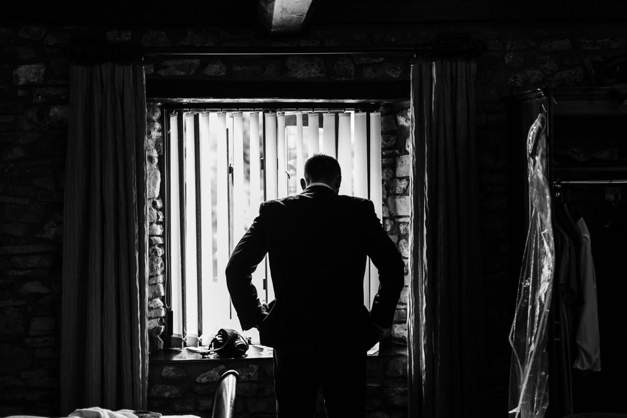 Atmospheric portrait of groom during preps