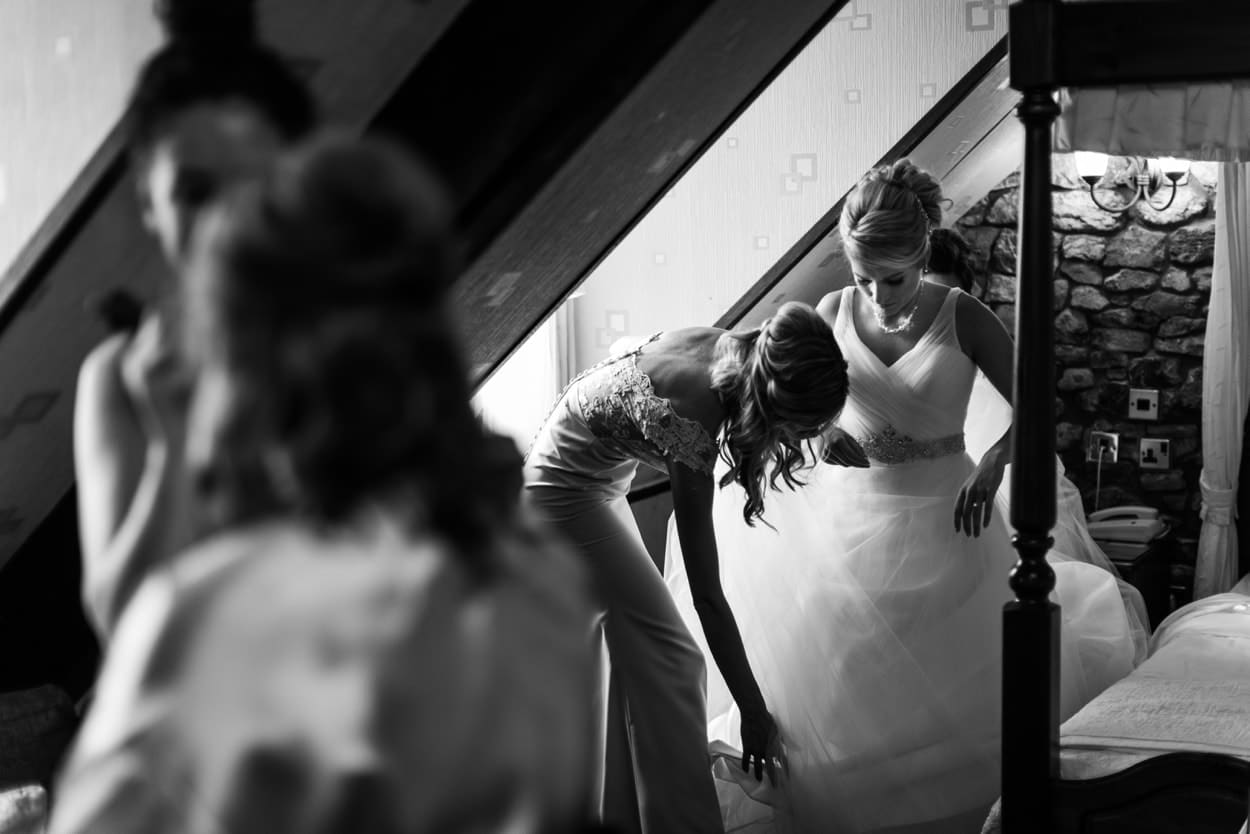 Bride putting on dress for a Wedding at St Donats Castle