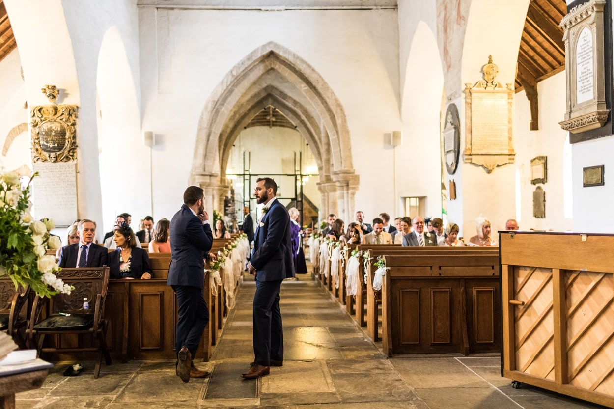 Groom waiting at alter of St Illtyds Church in Llantwit Major, South Wales