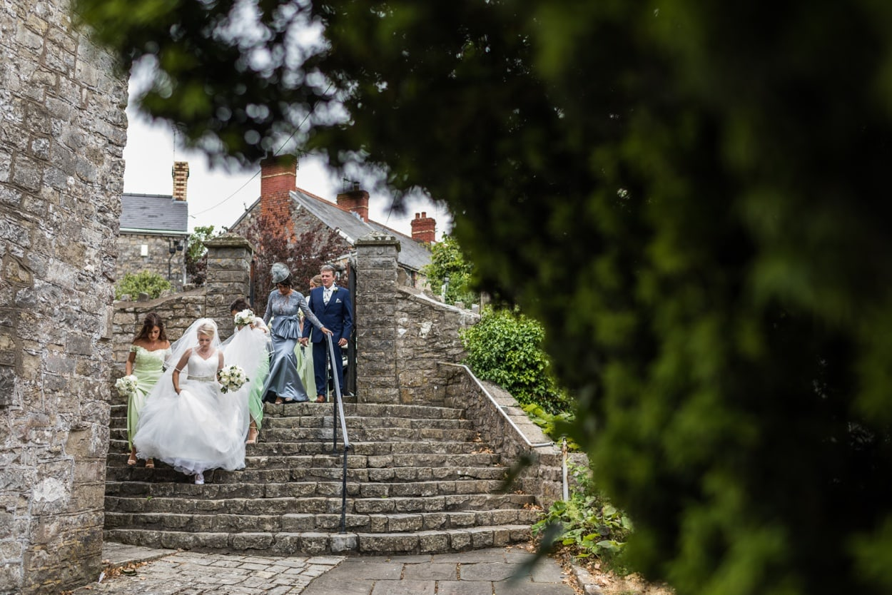 Bride desending steps at St Illtyds Church in Llantwit Major, South Wales