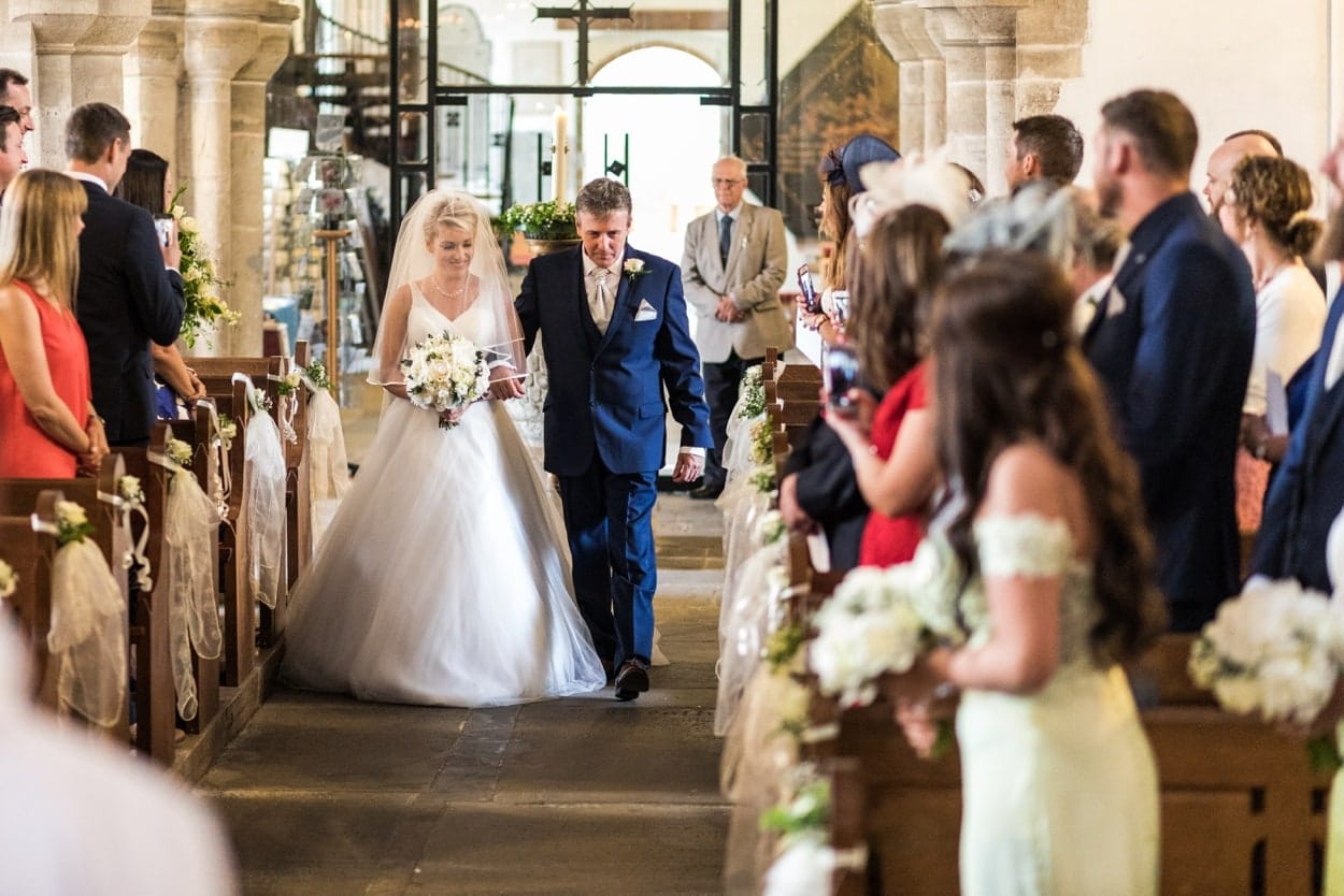 Father and bride coming down the aisle of St Illtyds Church in Llantwit Major, South Wales